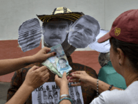"Opponents to the government place Bolivar banknotes on dummies depicting Venezuelan President Nicolas Maduro (C), Venezuelan Defense Minister Vladimir Padrino (R), and the former speaker of the Venezuelan National Assembly, Diosdado Cabello, as they prepare to burn them during the traditional ""burning of Judas"" on Easter Day at Chacao neighborhood, …"