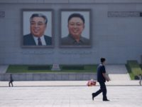 A man holding a bunch of flowers walks past the portraits of late North Korean leaders Kim Il Sung and Kim Jong Il, on Kim Il Sung square in Pyongyang on June 20, 2019, as Chinese President Xi Jinping visits the country. - Xi Jinping started a historic visit in …