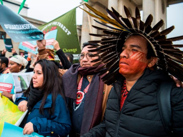 """Indigenous leaders from Latin America, Indonesia and Africa, known as """"The Guardians of the Forest"""", display placards during a protest in front of Berlin's Brandenburg Gate on November 1, 2017. At R is a member of Brazil's amazonian Tuxa tribe. The demonstrators, on their way to the COP23 UN Climate …"""