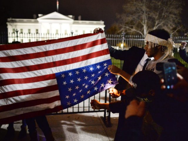 Protesters try unsuccessfully to burn an upside down US flag during a protest outside the White House in Washington, DC on November 25, 2014, one day after a grand jury decision not to prosecute a white police officer for the killing of an unarmed black teen in Ferguson, Missouri. AFP …