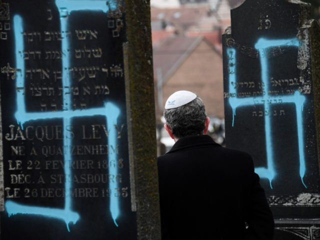 Jews - A man walks by graves vandalised with swastikas at the Jewish cemetery in Quatzenheim, on February 19, 2019, on the day of a nationwide marches against a rise in anti-Semitic attacks. - Around 80 graves have been vandalised at the Jewish cemetery in the village of Quatzenheim, close …