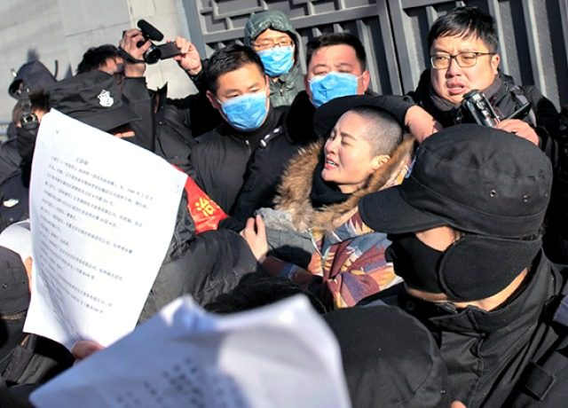 Chinese police and security personnel surround Li Wenzu, wife of human rights lawyer Wang Quanzhang, as she protests the criminal justice system on Dec. 28. (Nicolas Asfouri/AFP/Getty Images)