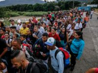 TOPSHOT - People queue to cross the Simon Bolivar international bridge from San Antonio del Tachira in Venezuela, to Cucuta, in Colombia on June 9, 2019. - Venezuelans alleviated their hardships a little with the partial reopening of the border bridges with Colombia. Thousands managed to cross on foot to …