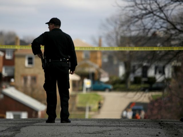 A police officer watches over the crime scene from a nearby corner April 4, 2009 in Pittsburgh, Pennsylvania. Five police officers were shot during a standoff with a suspect in the Stanton Heights neighborhood of Pittsburgh, after police responded to a domestic dispute. (Photo by Ross Mantle/Getty Images)