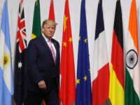 US President Donald Trump walks past G20 member flags as he is welcomed by Japanese Prime Minister Shinzo Abe prior to the family photo at the G20 Osaka Summit in Osaka on June 28, 2019. (Photo by Ludovic MARIN / POOL / AFP) (Photo credit should read LUDOVIC MARIN/AFP/Getty Images)