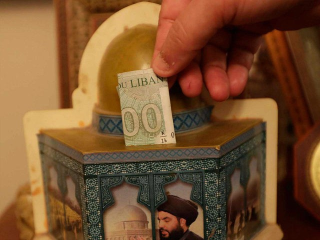 A man drops a bank note in a donation box in the form of Jerusalem's Dome of the Rock mosque, and bearing a portrait the head of Lebanon's militant Shiite movement Hezbollah, in a southern suburb of the capital Beirut on June 3, 2019. - The militant Shiite organisation, a …