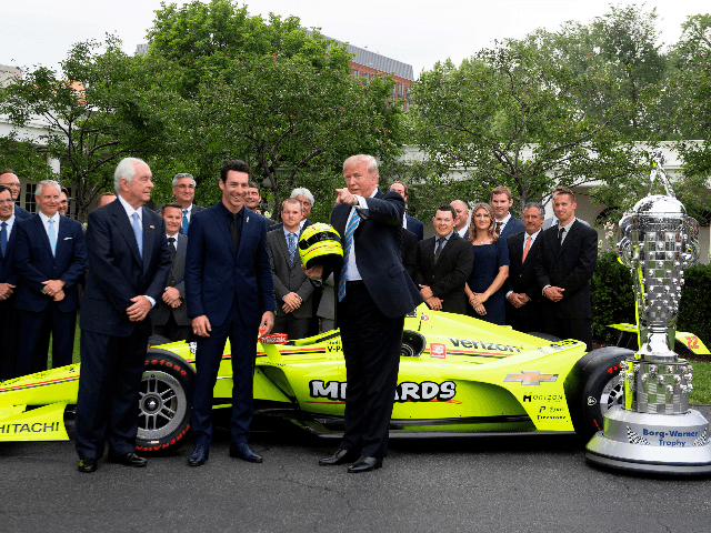 US President Donald Trump greets members of Team Penske, as he recieves a helmet from driver Simon Pagenaud (C) the winner of the 103rd Indianapolis 500 and Roger Penske (L), at the White House in Washington, DC, on June 10, 2019. (Photo by Jim WATSON / AFP) (Photo credit should …