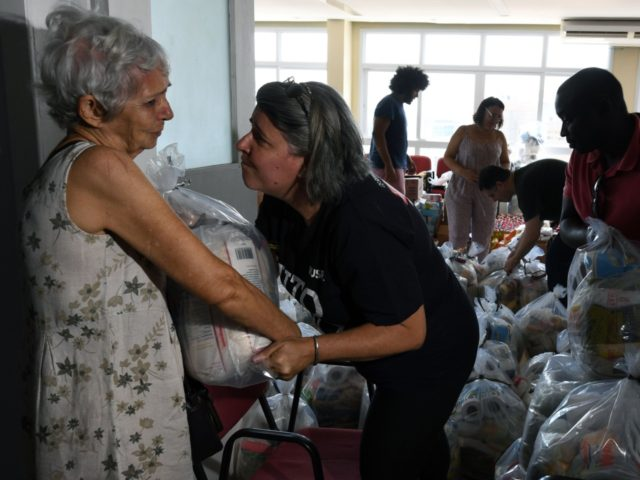 A volunteer comforts an elderly woman at Rio de Janeiro's state public servants union as she gives her a food and supplies donation prepared by workmates and volunteers, since some of them haven't received their payment for several months, in Rio de Janeiro, Brazil on December 27, 2016. Rio de …