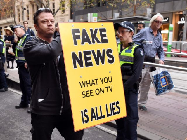 A man holds up a 'Fake News' placard as members of the Australian Liberty Alliance (ALA) and supporters protest outside the British consulate in support of jailed British right-wing activist and former leader to the English Defence League (EDL) Tommy Robinson, aka Stephen Christopher Yaxley-Lennon, in Melbourne on June 9, …