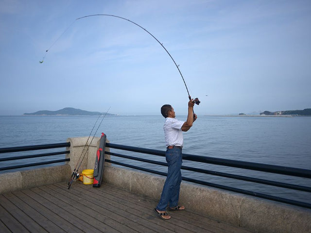 A man casts his fishing rod in Weihai, east China's Shandong province on July 22, 2014. Tens of thousands of domestic tourists visit the coastal city during summer. AFP PHOTO / WANG ZHAO (Photo credit should read WANG ZHAO/AFP/Getty Images)