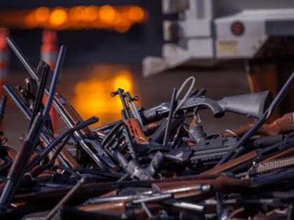 Molten slag is seen behind a pile of approximately 3,500 confiscated guns about to be destroyed at the Gerdau Steel Mill understand supervision of the Los Angeles County Sheriffs Department and other law enforcement agencies on July 19, 2018 in Rancho Cucamonga, California. The weapons were seized in criminal investigations, …