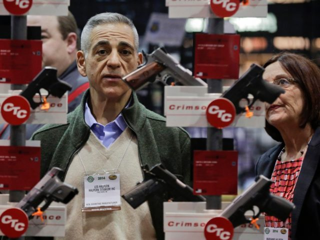 FILE - In this Jan. 14, 2014, file photo, knife manufacturers Les Halpern, left, and Marianne Halpern, of Three Rivers, Mass., examine a display of various handguns outfitted with laser sights on display at the Crimson Trace exhibit during the Shooting Hunting and Outdoor Trade Show in Las Vegas. The …