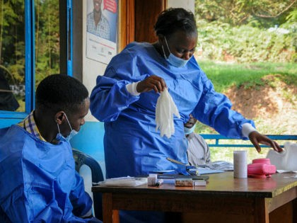 A health worker puts on her protective clothing before vaccinating people against Ebola at the hospital in the village of Kagando, near the border with Congo, in western Uganda Saturday, June 15, 2019. The World Health Organization (WHO) in Uganda said Saturday that it has started ring vaccination of all …