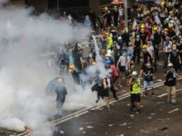 A protester throws a tear gas canister fired by police during a rally against a controversial extradition law proposal outside the government headquarters in Hong Kong on June 12, 2019. - Violent clashes broke out in Hong Kong on June 12 as police tried to stop protesters storming the city's …