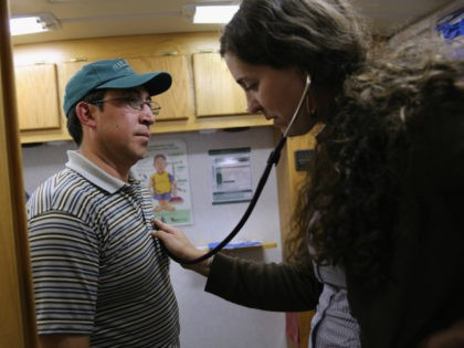 Physician's assistant Stephanie Miller checks the heart rate of an immigrant farm worker from Mexico during mobile clinic visit to a farm on April 30, 2013 in Brighton, Colorado. Salud family Health Centers sends a mobile clinic to farms throughout northeastern Colorado to serve the migrant population, many of whom …