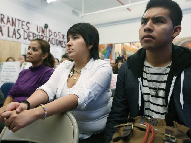 Undocumented immigrant Oscar Rodriguez (R), originally from Mexico, watches with Yenny Quispe (C), who is from Peru and received her Green Card two days ago, during a watch party of President Barack Obama's speech on immigration on January 29, 2013 in New York City. Obama called for immigration reform and …