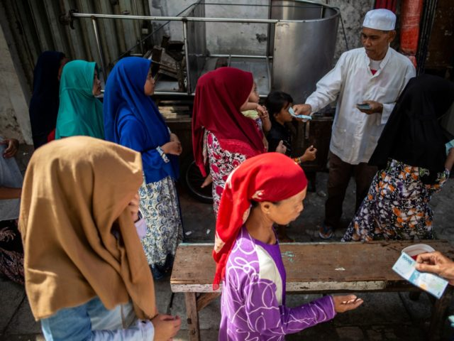 Indonesians queue up for charitable cash handouts in Surabaya on May 31, 2019, ahead of Eid al-Fitr marking the end of the holy fasting month of Ramadan. (Photo by JUNI KRISWANTO / AFP) (Photo credit should read JUNI KRISWANTO/AFP/Getty Images)