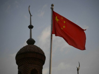 This photo taken on June 4, 2019 shows the Chinese flag flying over the Juma mosque in the restored old city area of Kashgar, in China's western Xinjiang region. - While Muslims around the world celebrated the end of Ramadan with early morning prayers and festivities this week, the recent …