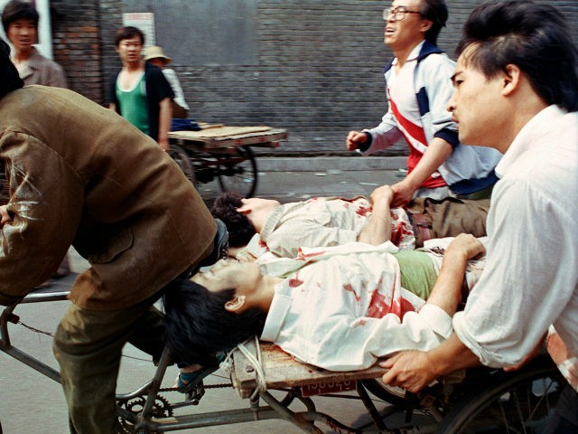 FILE - In this June 4, 1989 file photo, a rickshaw driver peddles wounded people, with the help of bystanders, to a nearby hospital in Beijing after they were injured during clashes with Chinese soldiers in Tiananmen Square. The crackdown ended a period of relative political openness, led to the …