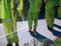 Men wearing neon-colored jail clothes signifying immigration detainees walk to pick up their lunches at the Theo Lacy Facility, a county jail which houses convicted criminals as well as immigration detainees, March 14, 2017 in Orange, California, about 32 miles (52km) southeast of Los Angeles. US President Donald Trumps first …