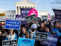 "Pro-choice activists hold signs in response to anti-abortion activists participating in the ""March for Life,"" an annual event to mark the anniversary of the 1973 Supreme Court case Roe v. Wade, which legalized abortion in the US, outside the US Supreme Court in Washington, DC, January 18, 2019. (Photo by …"