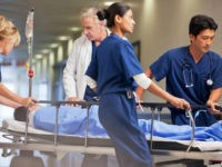 Doctor and nurses wheeling patient in gurney through hospital corridor - stock photo