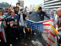 "Iranian demonstrators burn a makeshift US flag during a rally in the capital Tehran, on May 10 2019. - Iranian foreign minister blamed the EU for the decline of Tehran's nuclear accord with world powers and insisted the bloc ""should uphold"" its obligations under the pact in which Iran agreed …"