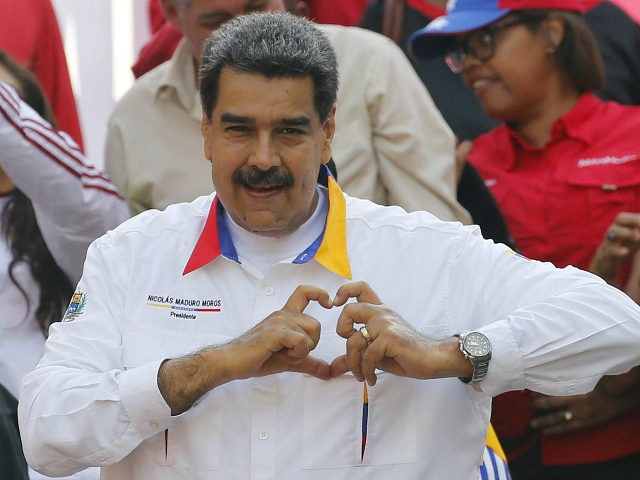 In this May 20, 2109 photo, Venezuela's President Nicolas Maduro flashes a hand-heart symbol to supporters outside Miraflores presidential palace in Caracas, Venezuela. Maduro said Thursday, May 23, 2019, that he iss inviting China's Huawei to help set up a 4G network in Venezuela, prompting opposition leader Juan Guaidó to …