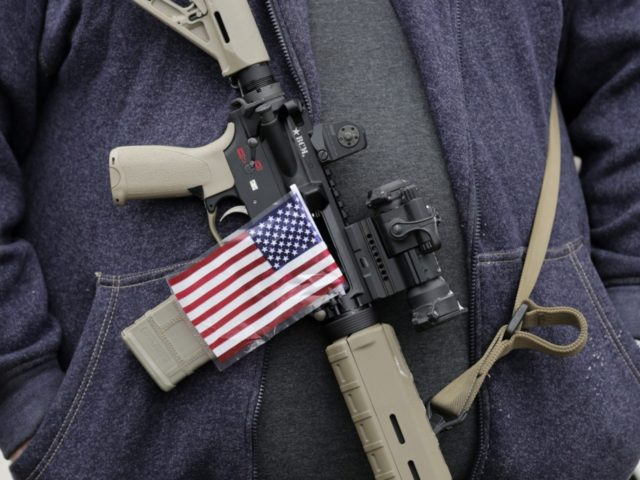 "A gun-rights activist carries his rifle with an American flag during a ""National Day of Resistance"" rally at the Utah State Capitol in Salt Lake City, Utah on Saturday, Feb. 23, 2013. Activists said they were were there to show their support for the U.S. Constitution and the 2nd Amendment. …"