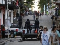 Municipal police trucks drive past strolling tourists, as they leave the Blue Parrot club, where several people were killed in early morning gunfire, in Playa del Carmen, Mexico, Monday, Jan. 16, 2017. Deadly gunfire broke out in the crowded beachfront nightclub throbbing with electronic music before dawn on Monday, setting …