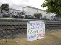 A sign opposing the Geo Group, the private contractor that operates the Northwest Detention Center, hangs on a fence outside the facility in Tacoma, Wash., Tuesday, July 10, 2018. The Trump administration rushed to meet a deadline Tuesday for reuniting dozens of youngsters forcibly separated from their families at the …