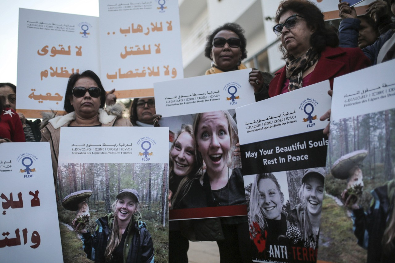 "Moroccan women carry photos of 28-year-old Norwegian Maren Ueland and 24-year-old Danish Louisa Vesterager Jespersen, during a candlelight vigil outside the Danish embassy in Rabat for the two Scandinavian university students who were killed in a terrorist attack in a remote area of the Atlas Mountains, Morocco, Saturday, Dec. 22, 2018. Moroccans gathered Saturday in front of the Norwegian and Danish embassies in Rabat in a candlelight vigil to honor two Scandinavian university students killed in a terrorist attack in the Atlas Mountains. Banner in Arabic reads ""No to terror, murder, rape"". (AP Photo/Mosa'ab Elshamy)"