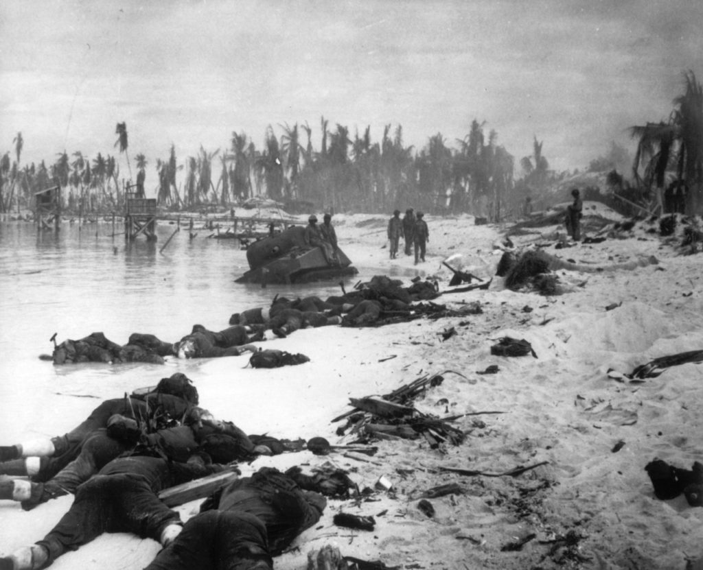 In this Nov. 1943 file photo, sprawled bodies are seen on the beach of Tarawa atoll testifying to the ferocity of the battle for this stretch of sand during the U.S. invasion of the Gilbert Islands. A nonprofit organization that searches for the remains of U.S. servicemen lost in past conflicts has found what officials believe are the graves of more than 30 Marines and sailors killed in one of the bloodiest battles of World War II. (AP Photo, FILE)
