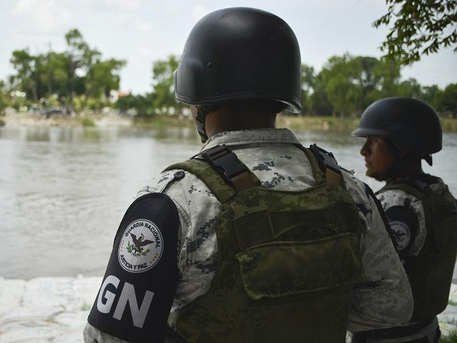 Mexican National Guards (GN) stand on the bank of the Suchiate River during a press tour organized by the GN near Ciudad Hidalgo, Mexico, Wednesday, July 3, 2019. A National Guard commander explained to the agents that they were there to support immigration enforcement, but not to interfere in the …
