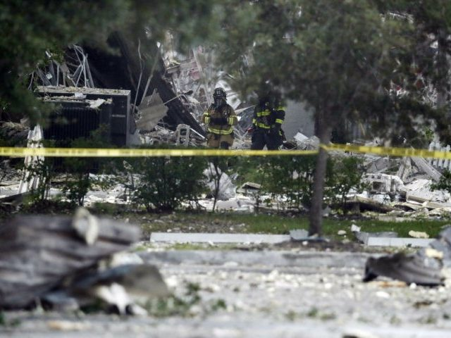 Firefighters walk through the remains of a building after an explosion on Saturday, July 6, 2019, in Plantation, Fla. Several people were injured after a vacant pizza restaurant exploded in the South Florida shopping plaza Saturday, according to police. The restaurant was destroyed, and nearby businesses were damaged. (AP Photo/Brynn …