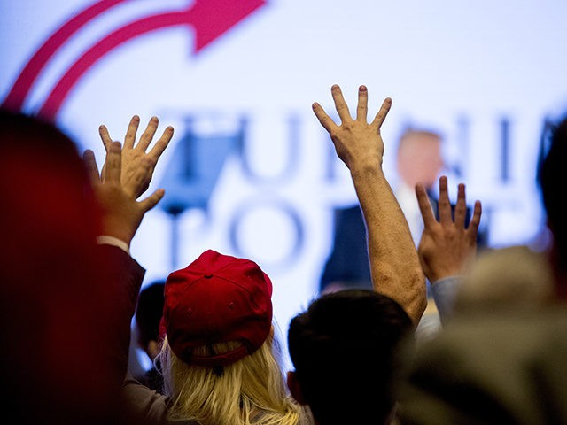 """Members of the audience hold up four fingers and chant """"Four More Years"""" as President Donald Trump, background, speaks at Turning Point USA Teen Student Action Summit at the Marriott Marquis in Washington, Tuesday, July 23, 2019. (AP Photo/Andrew Harnik)"""