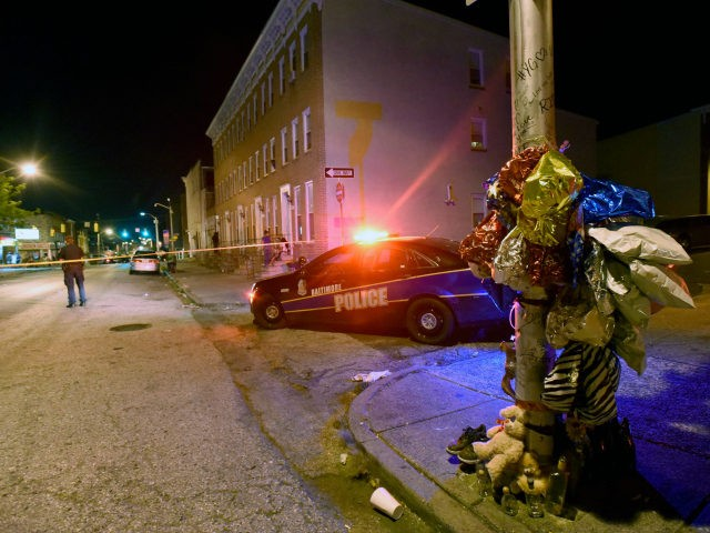 A previously created memorial, right, stands as Baltimore police work at a scene where multiple people were shot in Baltimore, Saturday night, Sept. 24, 2016. Police said that none of the shootings were fatal. (AP Photo/Steve Ruark)