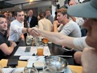 Democratic presidential candidate South Bend Mayor Pete Buttigieg shakes hands with a patron at the Revolution Taproom & Grill as he campaigns, Friday, July 12, 2019, in Rochester, N.H. (AP Photo/Charles Krupa)