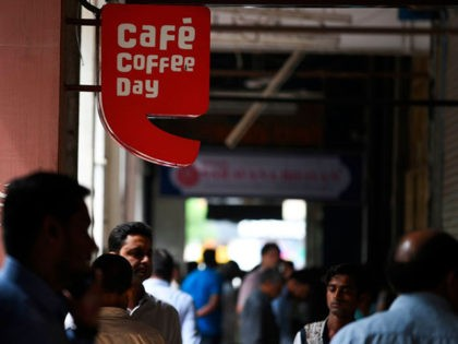 Pedestrians walk near the logo of Indian coffee retail chain 'Cafe Coffee Day' outside an outlet in New Delhi on July 30, 2019. - Indian police on July 30 launched a major hunt for one of the country's richest men, coffee tycoon V.G. Siddhartha, amid mounting fears for his safety. …