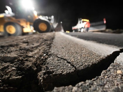 Highway workers repair a hole that opened in the road as a result of the July 5, 2019 earthquake, in Ridgecrest, California, about 150 miles (241km) north of Los Angeles, early in the morning on July 6, 2019. - Southern California was hit by its largest earthquake in two decades …
