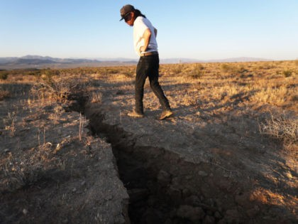 RIDGECREST, CALIFORNIA - JULY 04: A local resident inspects a fissure in the earth after a 6.4 magnitude earthquake struck the area on July 4, 2019 near Ridgecrest, California. The earthquake was the largest to strike Southern California in 20 years with the epicenter located in a remote area of …