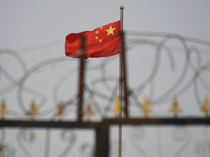TOPSHOT - This photo taken on June 4, 2019 shows the Chinese flag behind razor wire at a housing compound in Yangisar, south of Kashgar, in China's western Xinjiang region. - A recurrence of the Urumqi riots which left nearly 200 people dead a decade ago is hard to imagine …