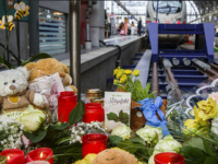 Flowers and candles lay near a track at the main train station in Frankfurt, Germany, Tuesday, July 30, 2019. An eight-year-old boy was pushed on the rails and died on Monday, July 29, 2019. (Frank Rumpenhorst/dpa via AP)