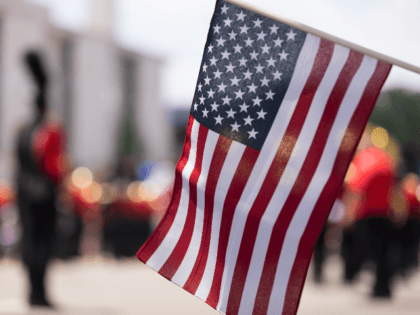 The American National Flag on the foreground with a marching band and buildings out of focus during a parade.
