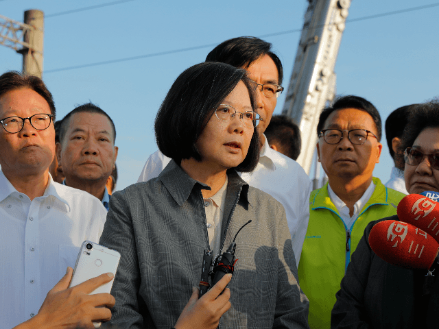 Taiwan's President Tsai Ing-wen (C) speaks after a briefing at Xinma station in Taiwan's northeastern Yilan county on October 22, 2018, a day after a Puyuma Express train derailed at high speed near the station. - At least 18 people have died after an express train derailed and flipped over …