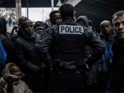 A policeman stand in front of Migrants waiting during the evacuation of a makeshift camp set up under Paris' ring road in the north of Paris' area of Porte de la Chapelle, on January 29, 2019, in an operation led by local authorities to shelter volunteer migrants in nearby gymnasiums …