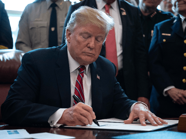 US President Donald Trump signs the first veto of his presidency, overriding a congressional resolution to secure emergency funds to build his much-vaunted wall on the US-Mexico border in the Oval Office at the White House in Washington, DC, on March 15, 2019. (Photo by NICHOLAS KAMM / AFP) (Photo …