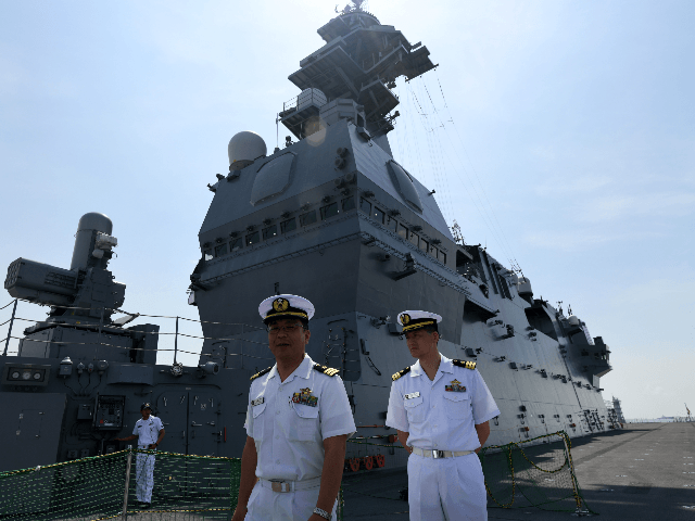 Japanese navy officers walk along the flight deck onboard the JS Izumo naval ship during a media tour at Changi Naval Base in Singapore on May 13, 2019. (Photo by Roslan RAHMAN / AFP) (Photo credit should read ROSLAN RAHMAN/AFP/Getty Images)