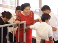 Philippine former first lady Imelda Marcos (in red) is helped by aides as she leaves after attending the proclamation of her daughter Senator Imee Marcos (not pictured), in Manila on May 22, 2019. - Allies of President Rodrigo Duterte stormed to a landslide victory in midterm polls, final results showed …