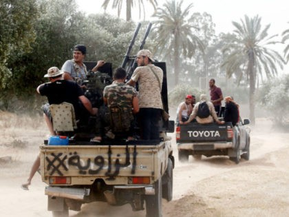 Fighters loyal to the Libyan internationally-recognised Government of National Accord (GNA) step up to the front during clashes against forces loyal to strongman Khalifa Haftar, on May 25, 2019, in the Airport Road Area, south of the Libyan capital Tripoli. (Photo by Mahmud TURKIA / AFP) (Photo credit should read …